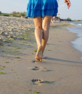 Woman barefoot walking beach